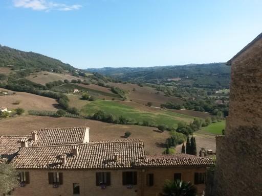 Colline oltre i tetti. Il borgo è su più livelli e lo sguardo raggiunge facilmente colline coltivate e boschi